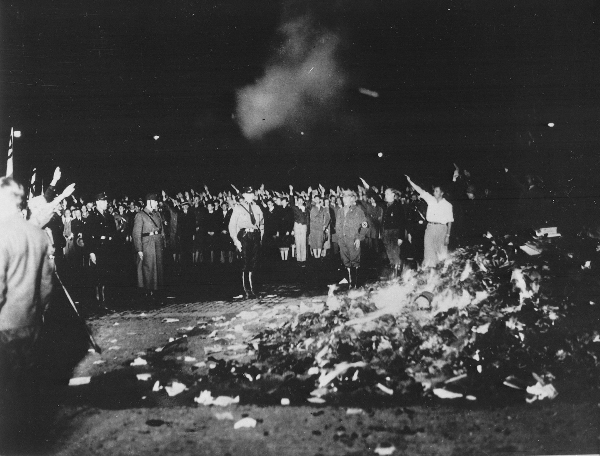 Thousands of books smoulder in a huge bonfire as Germans give the Nazi salute during the wave of book-burnings that spread throughout Germany.